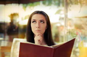 28913241 - young woman choosing from a restaurant menu
