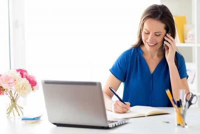 Woman on phone using laptop